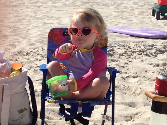 Sure, looks like she is relaxing, but she is just as neurotic as her father.  Notice the feet curled up on the chair to not touch the beach, the calming container of Pirates Booty, the sunglasses that were called for nonstop until they were presented?  She's a mess sometime